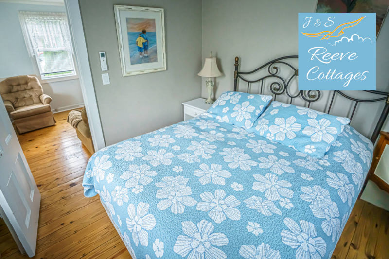 Premier Waterfront Cottage 3 shows bedroom one with queen bed, dresser, wall mount air conditioning and heat