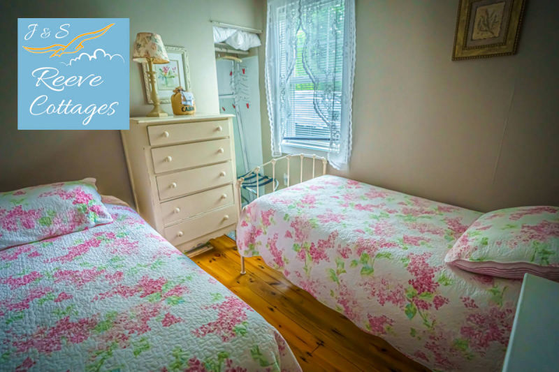 Premier Waterfront Cottage 3 shows bedroom two with 2 twin beds, dresser, wall mount air conditioning and heat